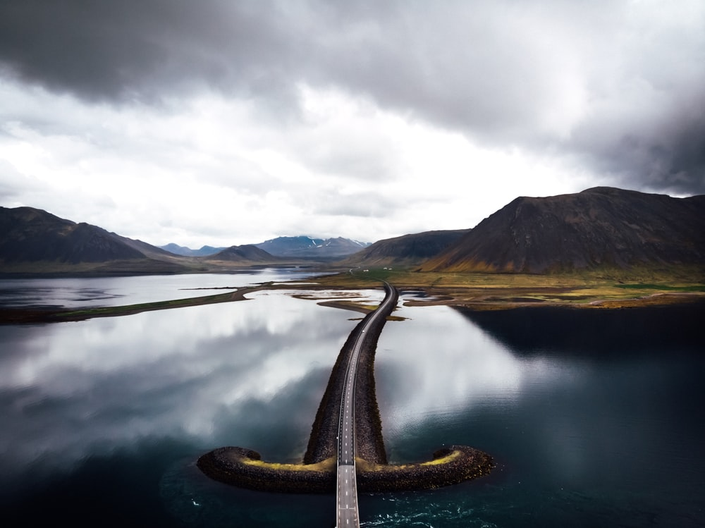 asphalt road in the middle of bodies of water