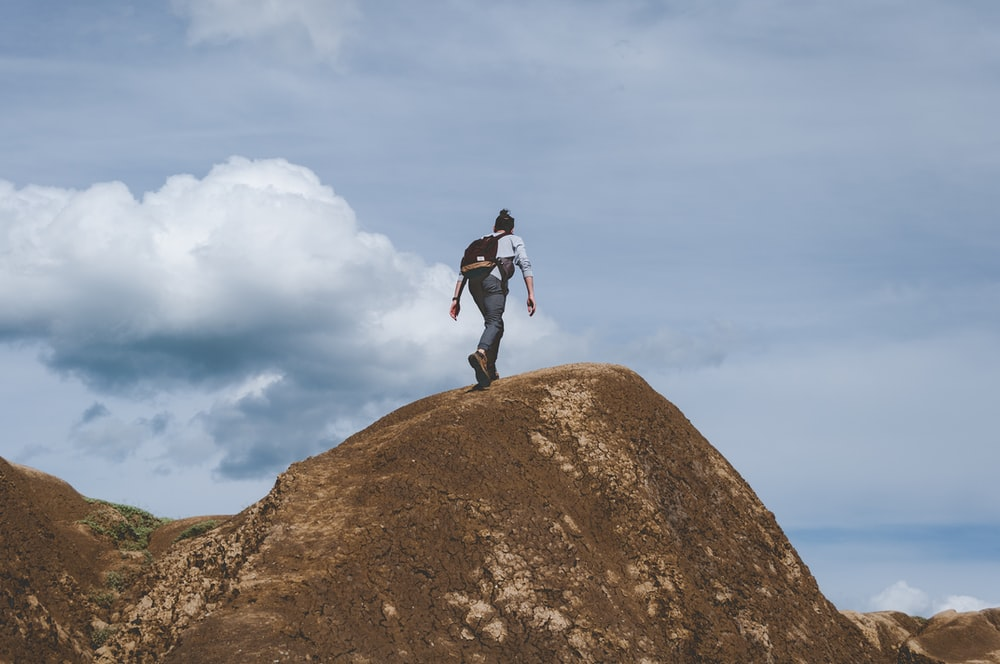 woman climbing on brown mountain during daytime