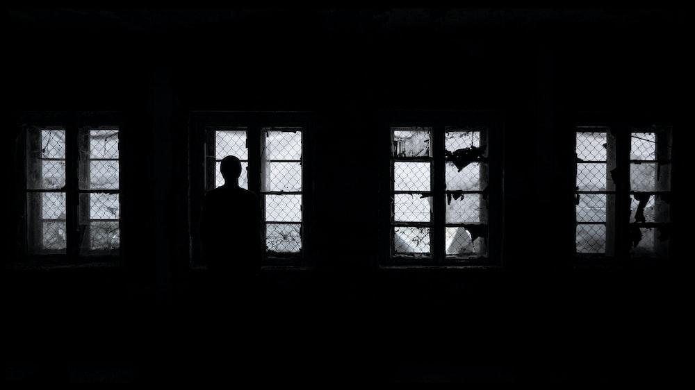 silhouette of man standing near window