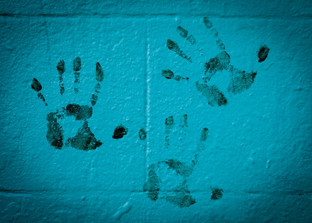three hand prints on white wall