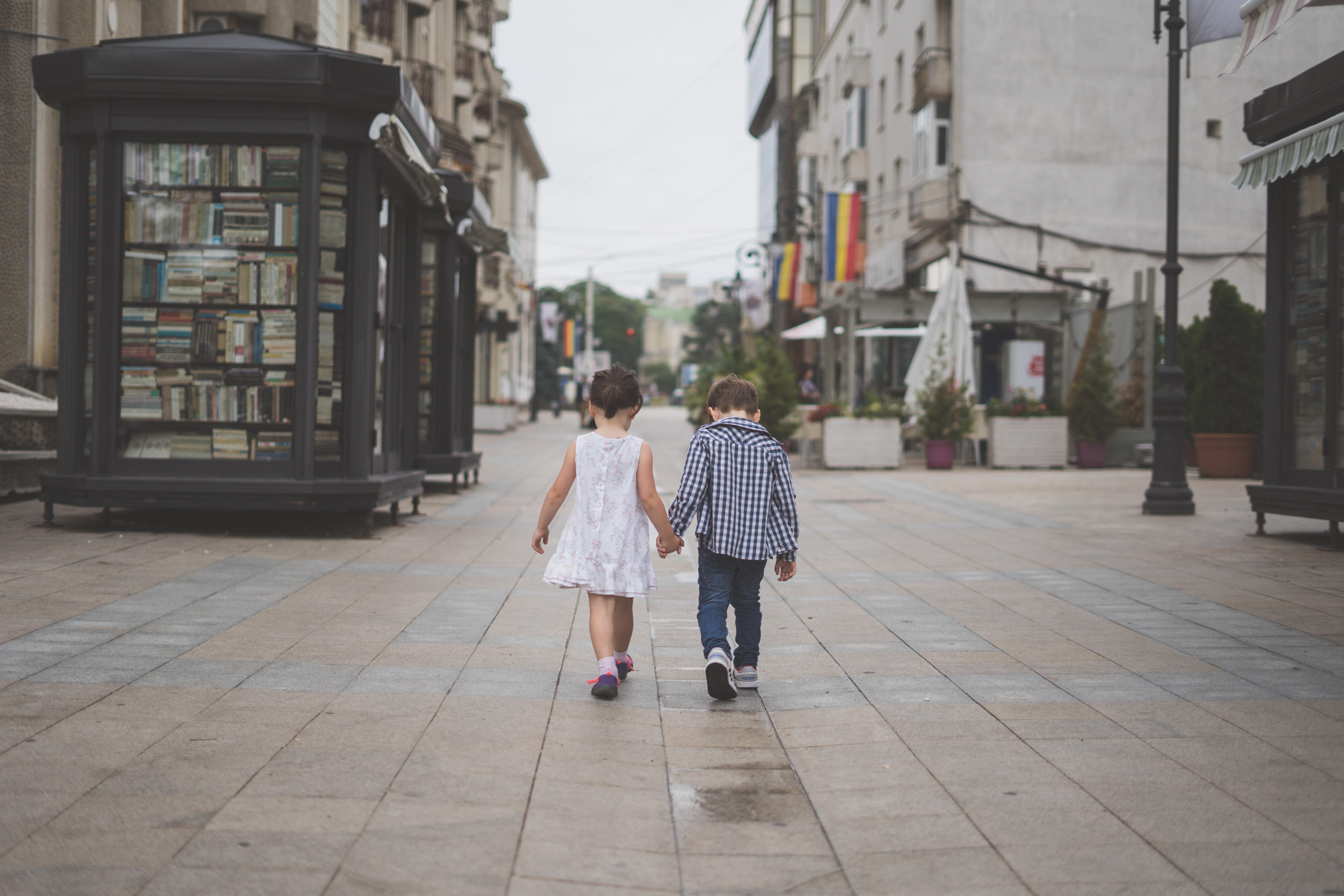 boy and girl holding hands while walking