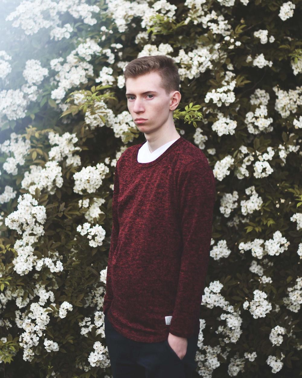 man standing against white petaled flower bed