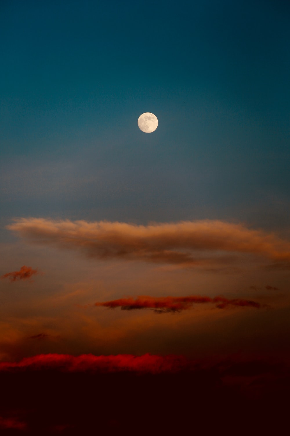 white, red, and blue sky with clouds and moon painting