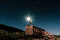 man standing on roof holding flashlight wallpaper