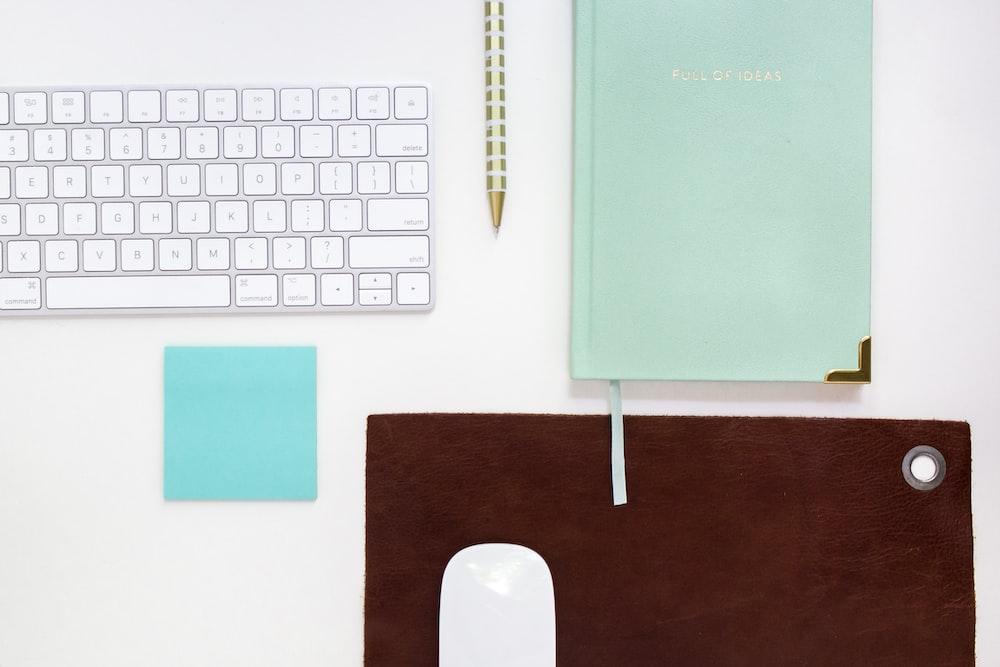 green book beside ballpoint pen and Apple magic keyboard