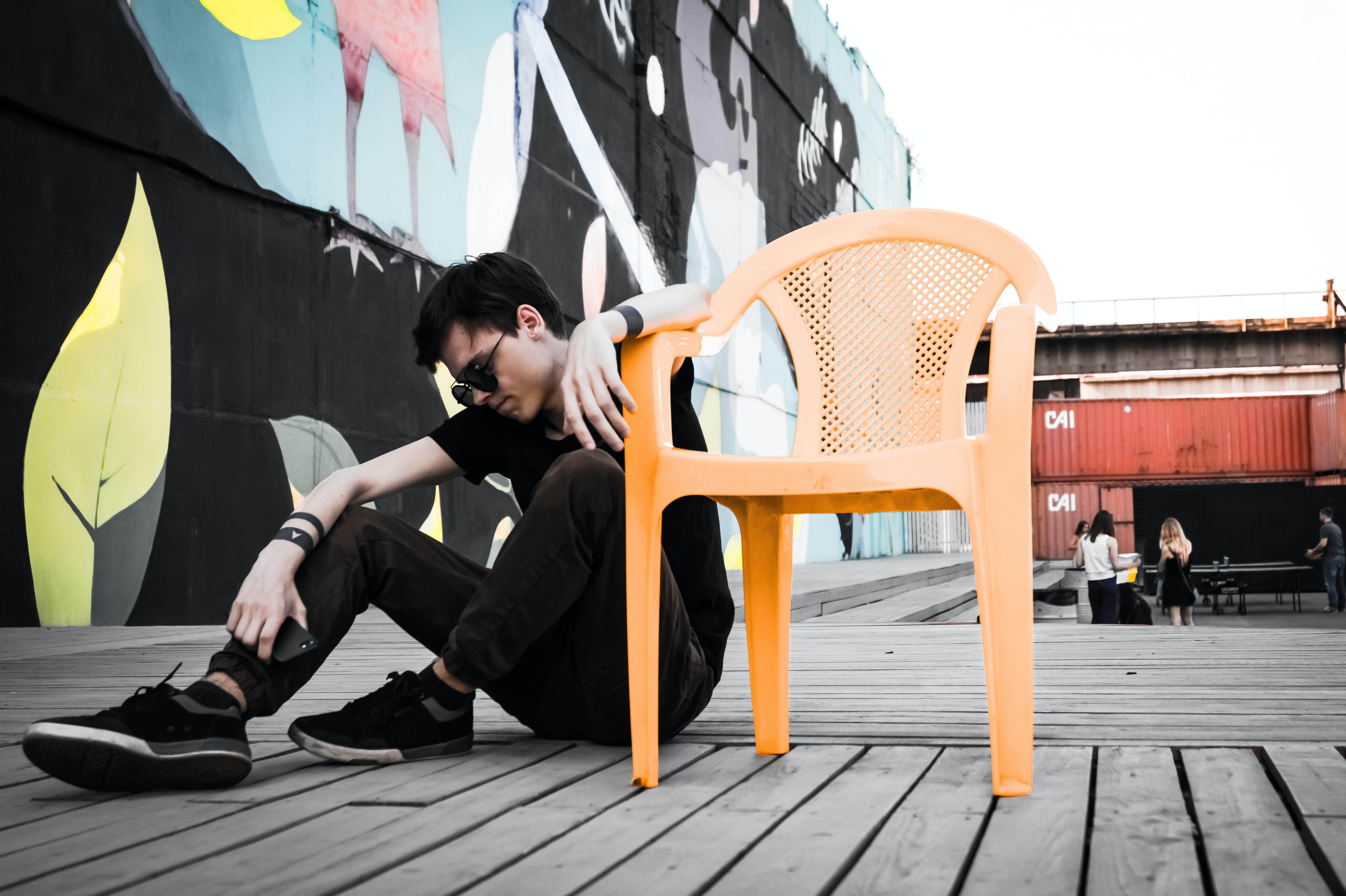 man sitting on floor beside empty orange plastic monobloc armchair at daytime