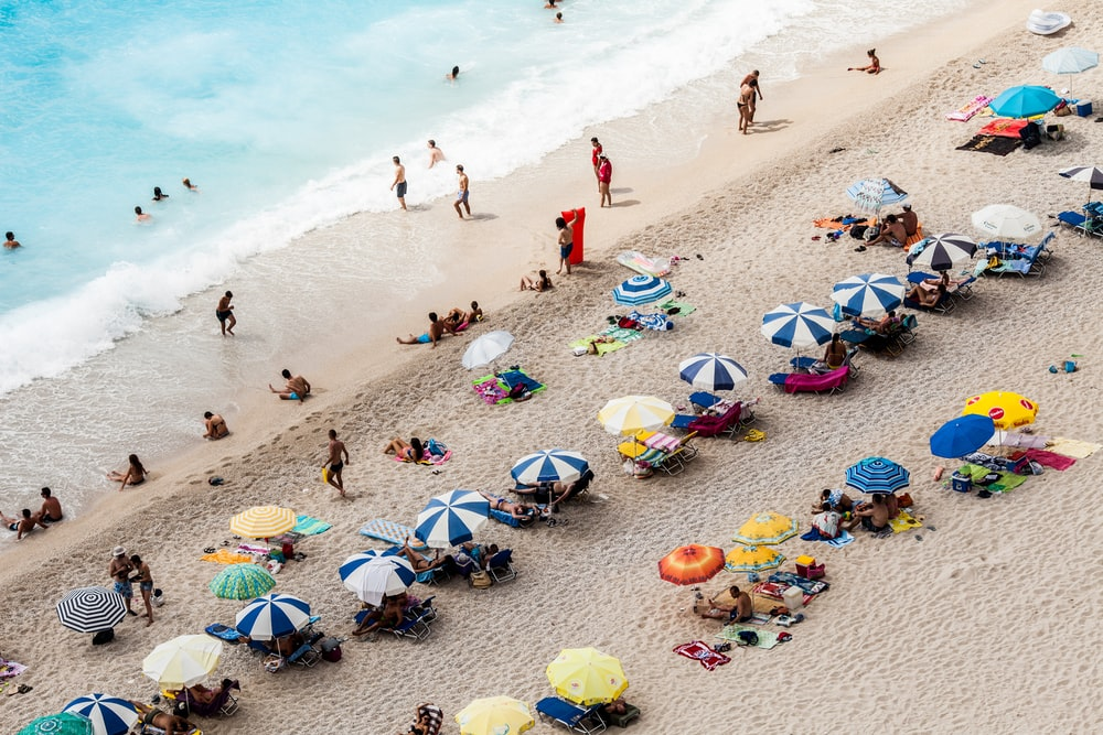 aerial view of parasols and people near beach