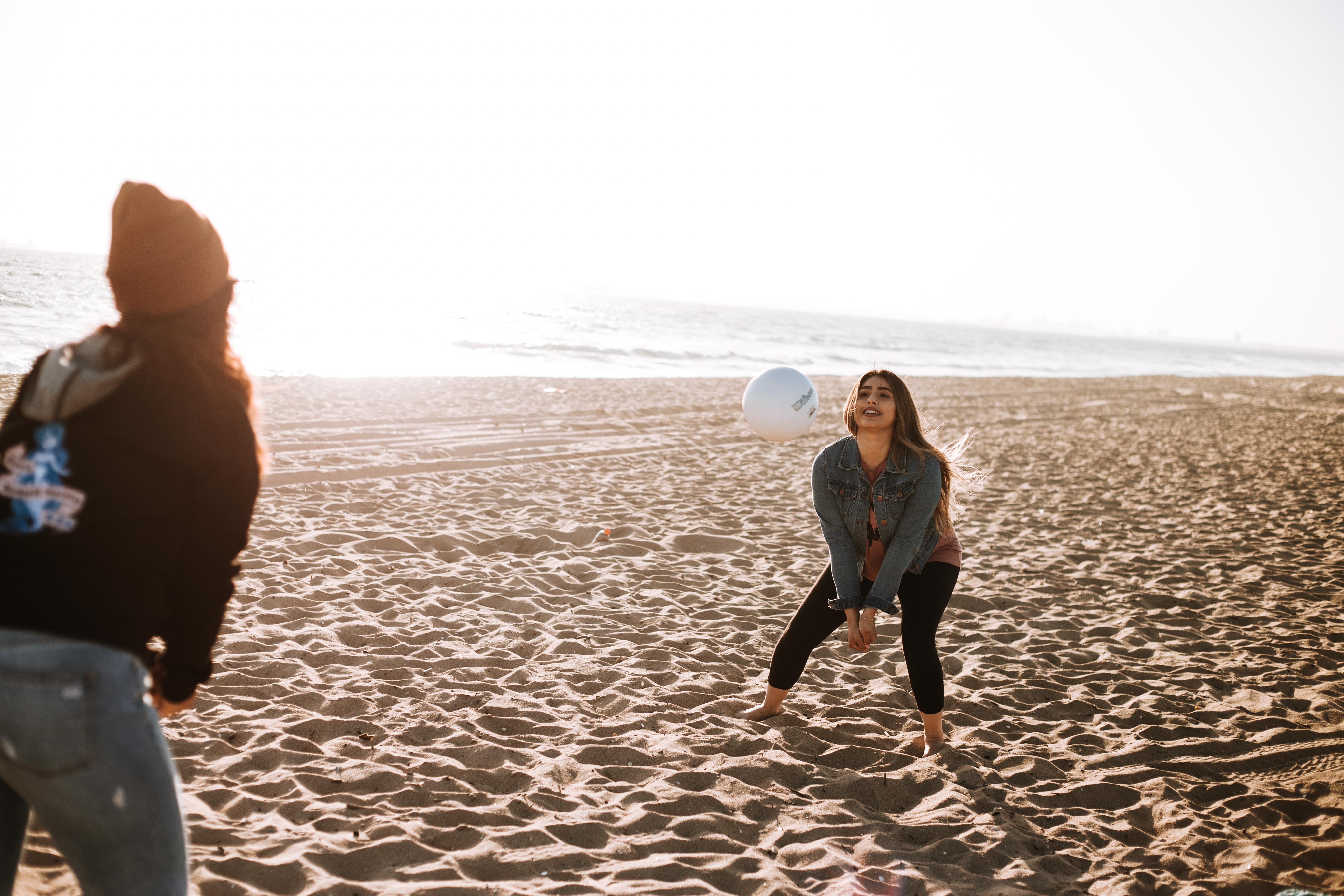two women playing volleyball on seashore