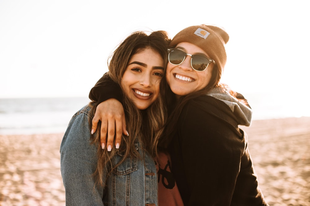 woman hugging other woman while smiling at beach