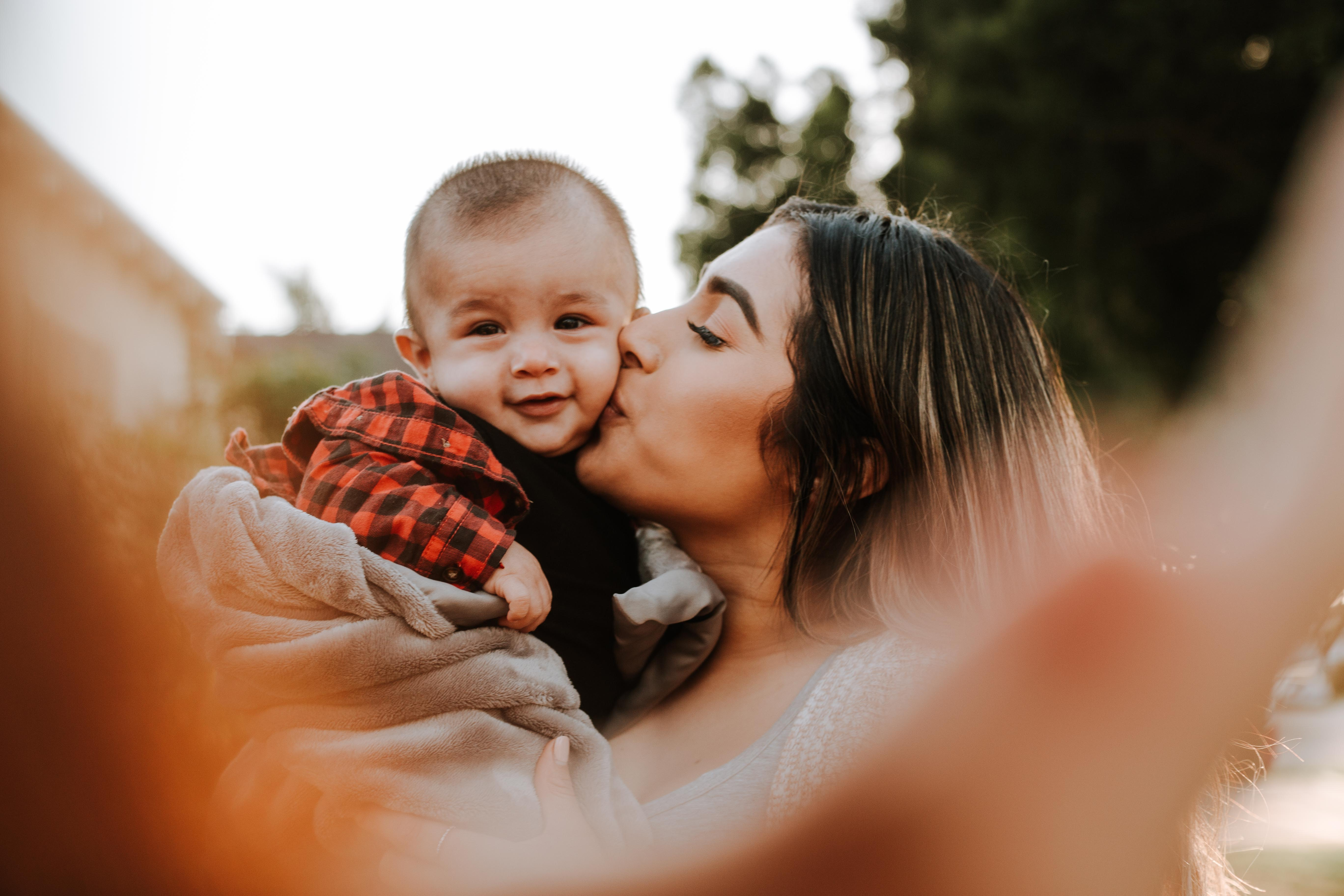 woman kiss a baby while taking picture