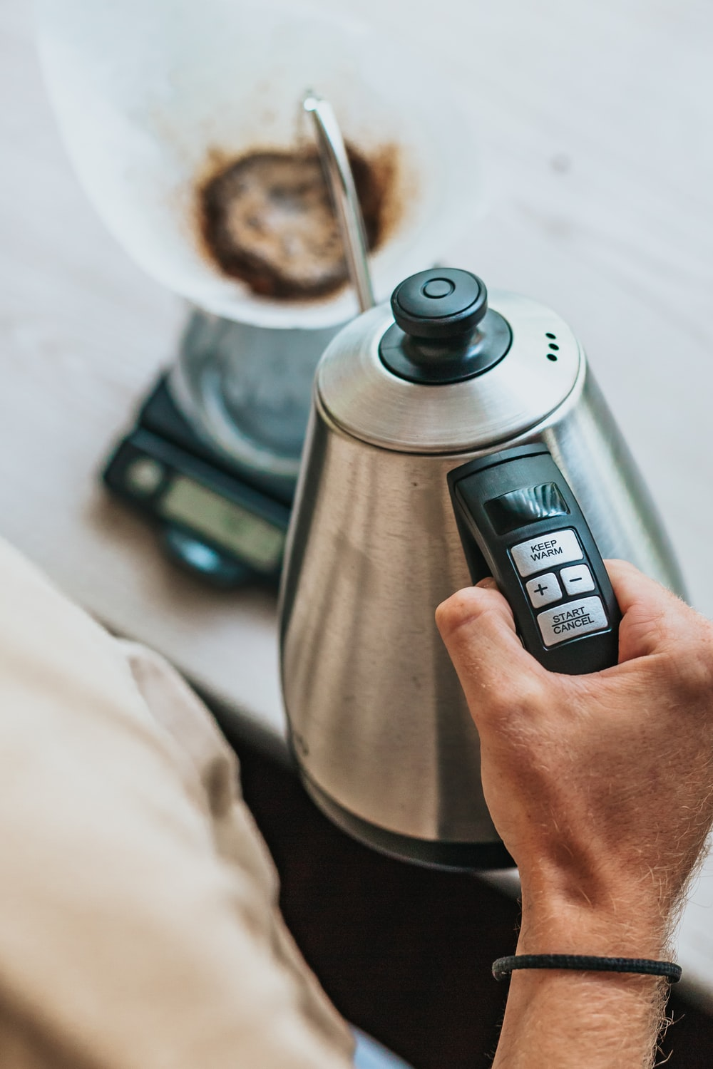 person holding silver stainless steel electric kettle