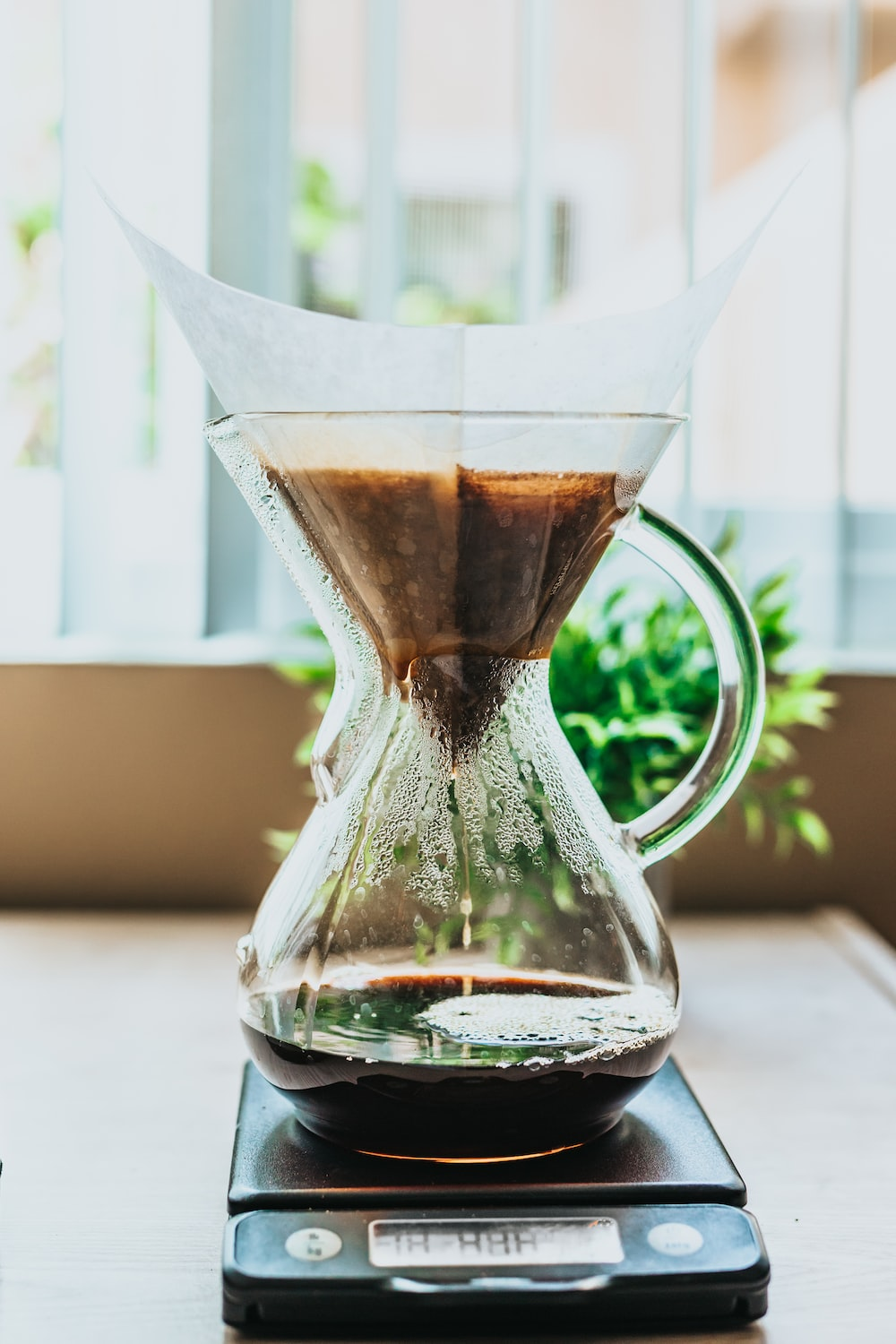 black pour-over coffeemaker on top of brown wood surface
