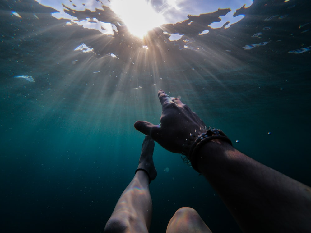 underwater photography of person soaking under sun rays