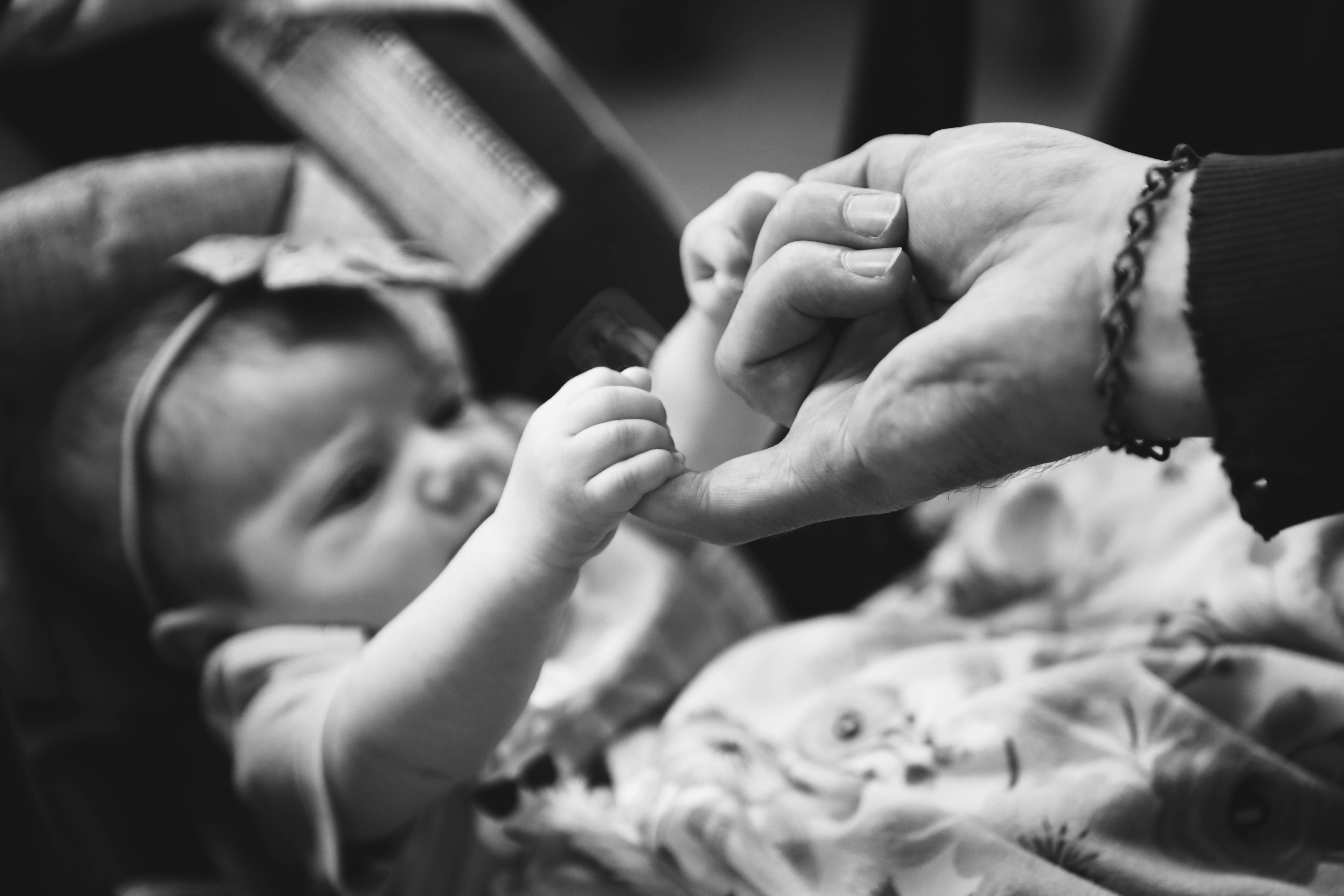 grayscale photo of child holding person finger