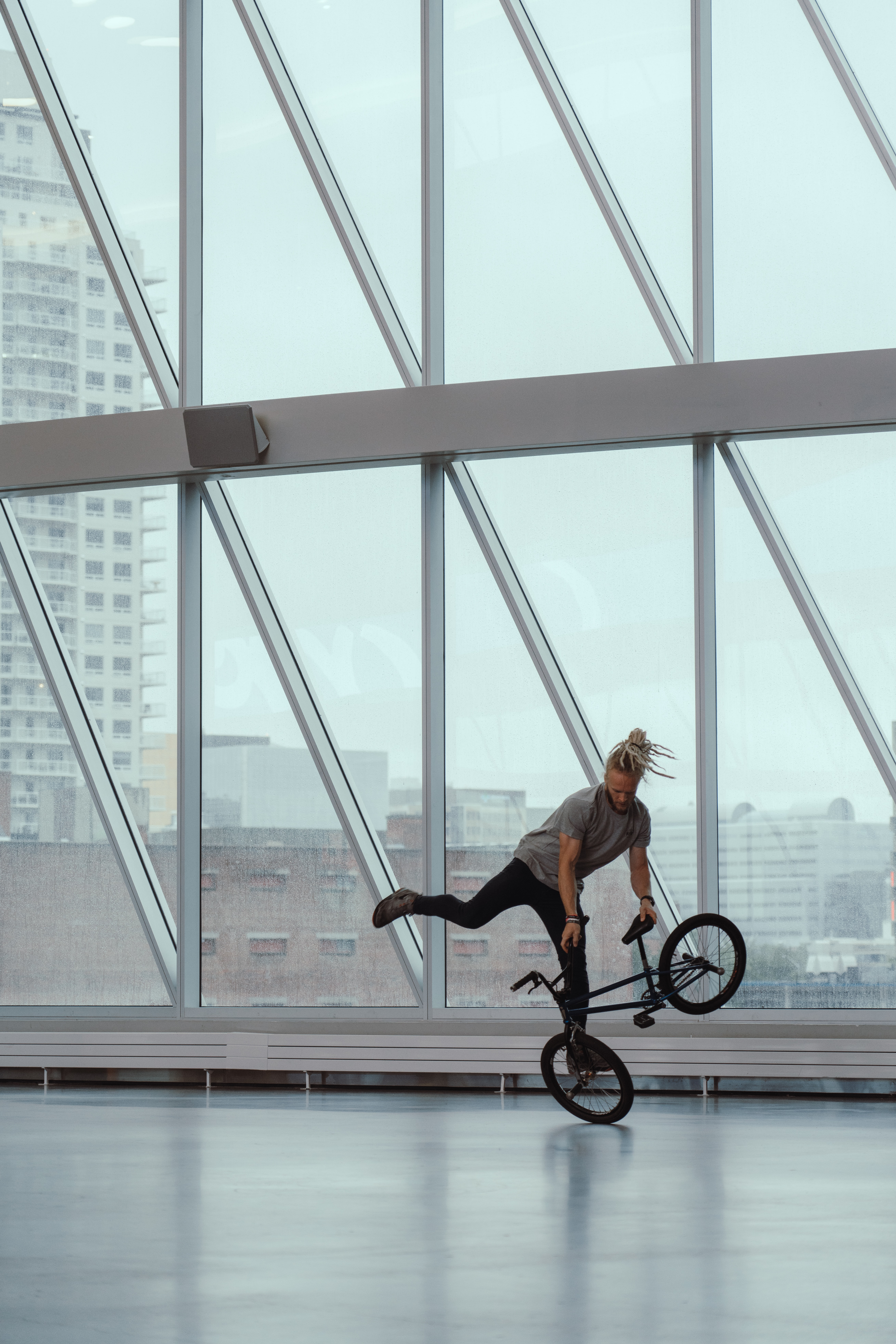 man riding bicycle doing stunts inside glass building during daytime