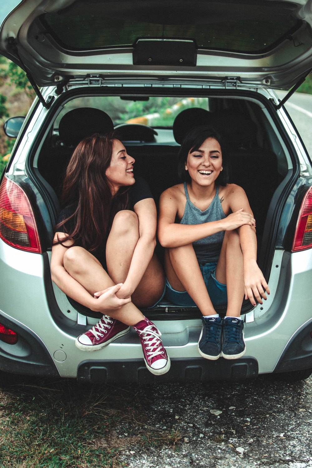 two women sitting at the back of the car