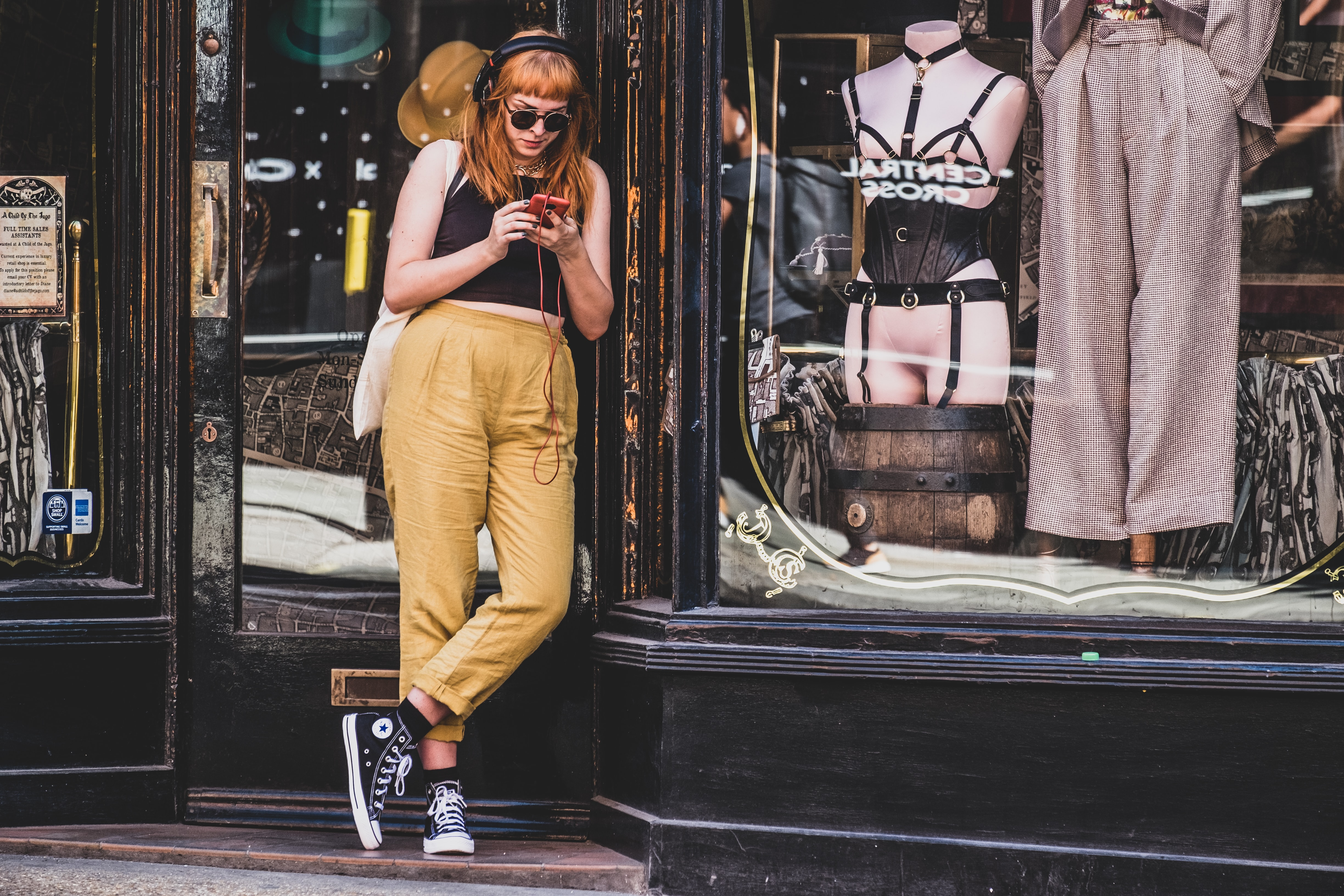 woman standing in front of store while using a smartphone