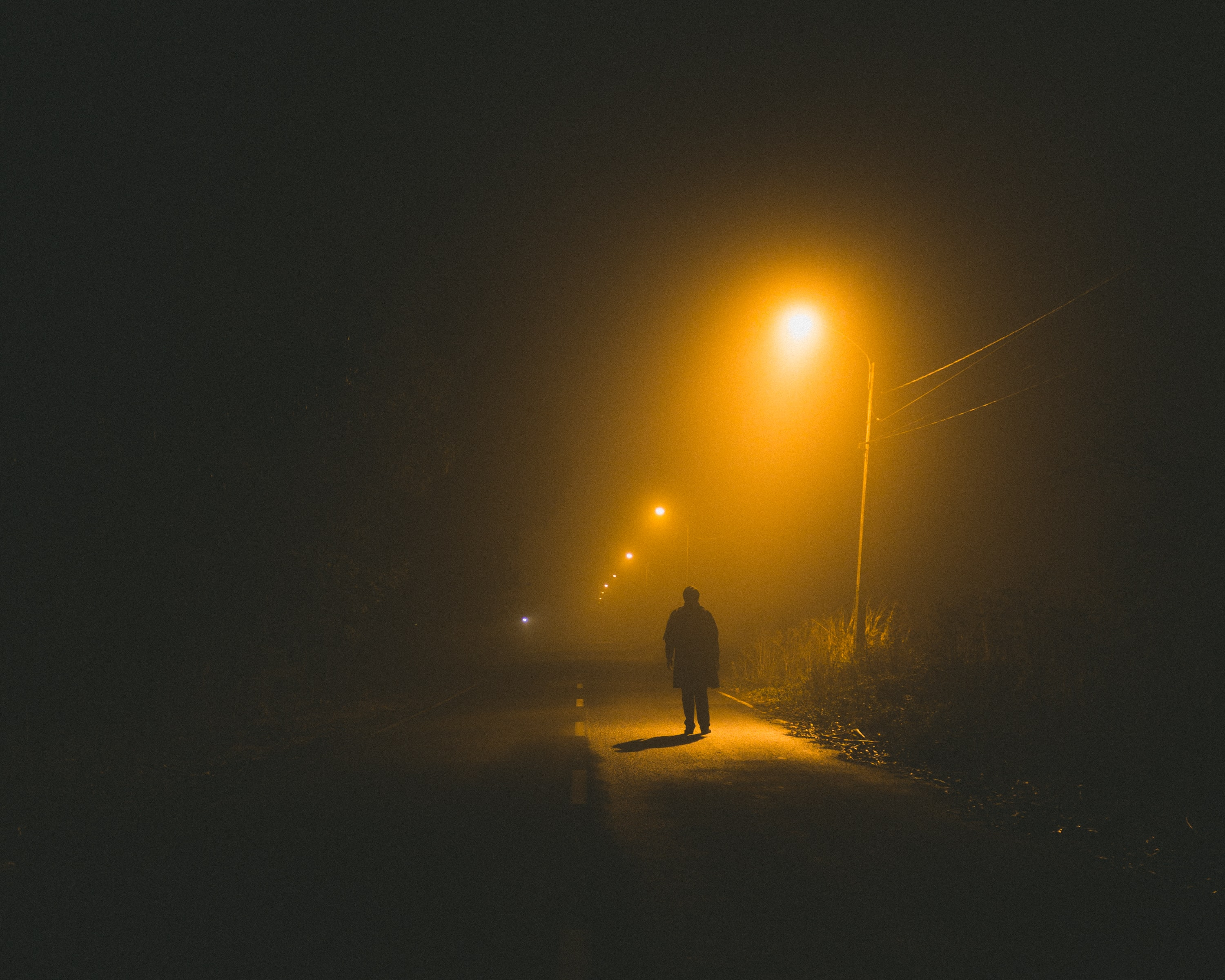person walking on road side at night time