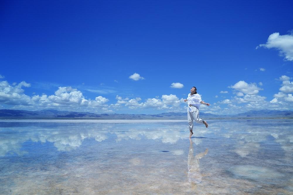 woman wearing white shirt walking on water during daytime