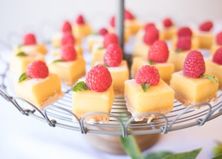 square strawberry cheesecake on round gray metal stand