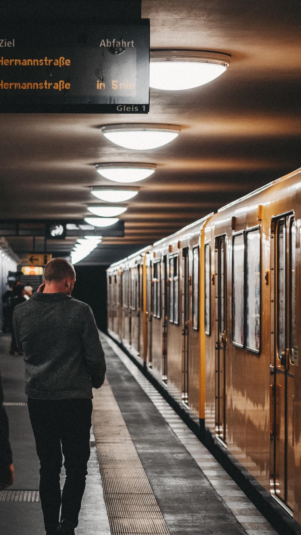 man walking near subway train