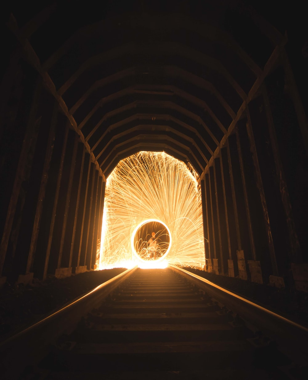 time lapse photography of steel wool fireworks inside tunnel