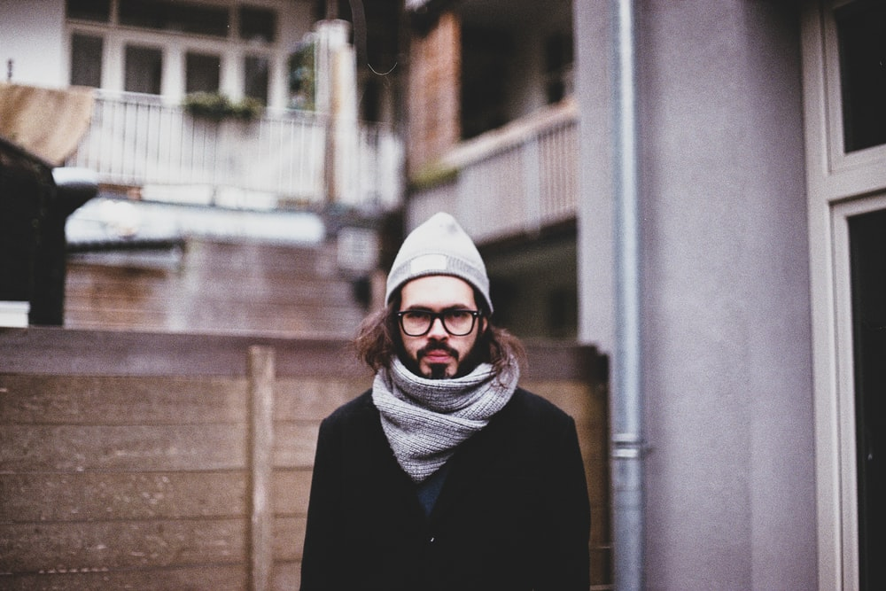 man wearing scarf near building