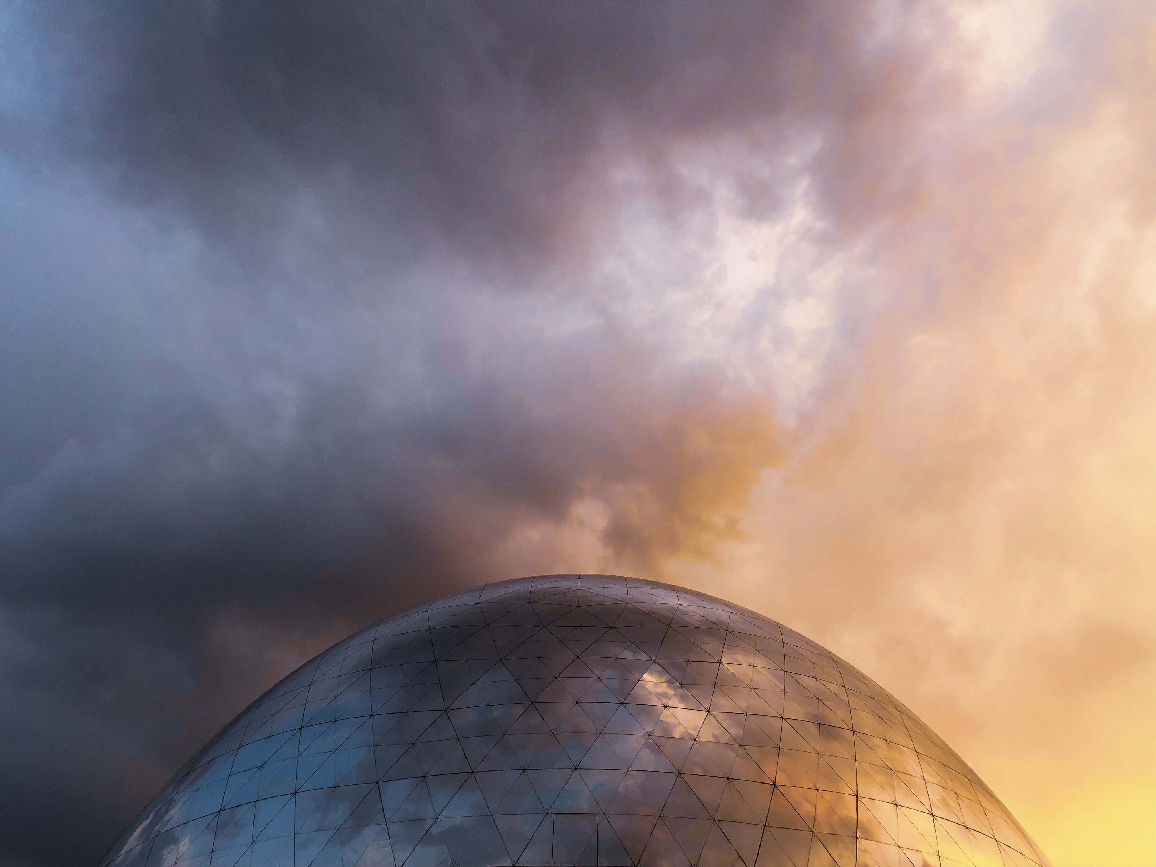 gray glass dome with dark clouds above it