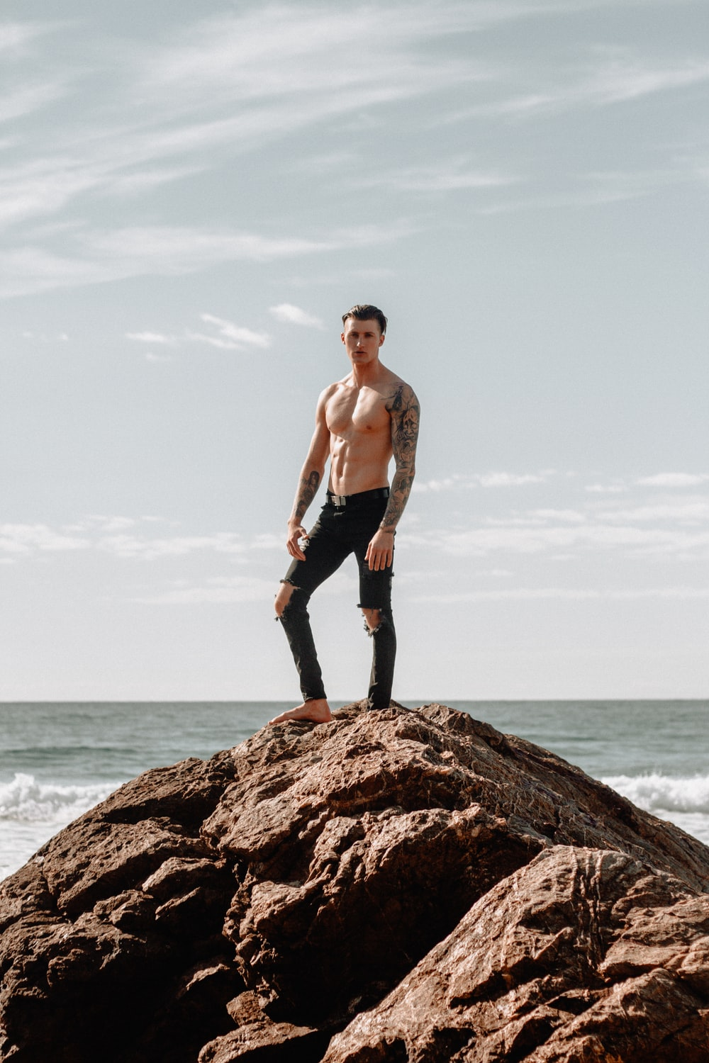 man in black pants standing on hill