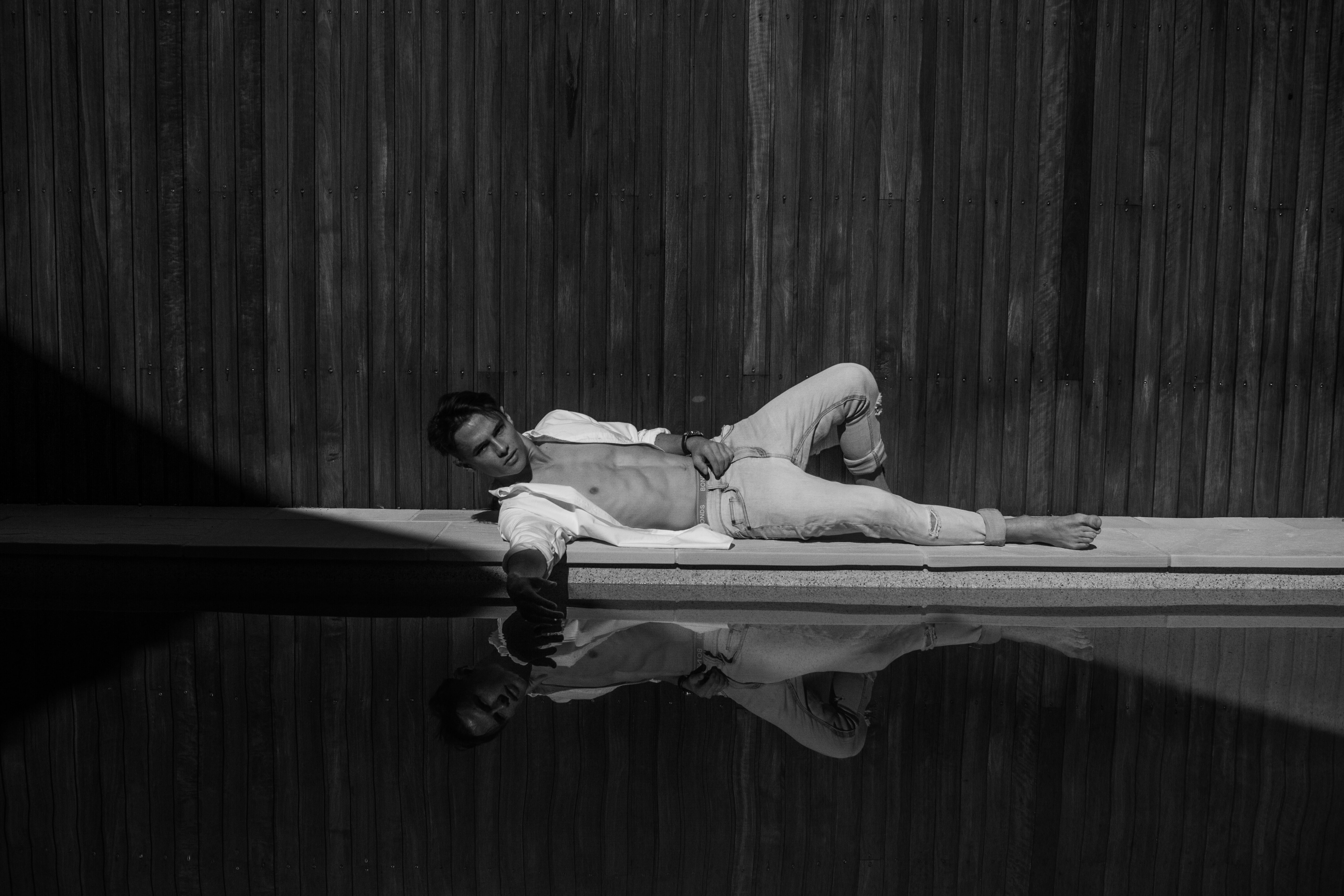 grayscale photography of man laying near swimming pool