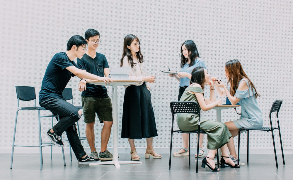 two men and four women meeting in office