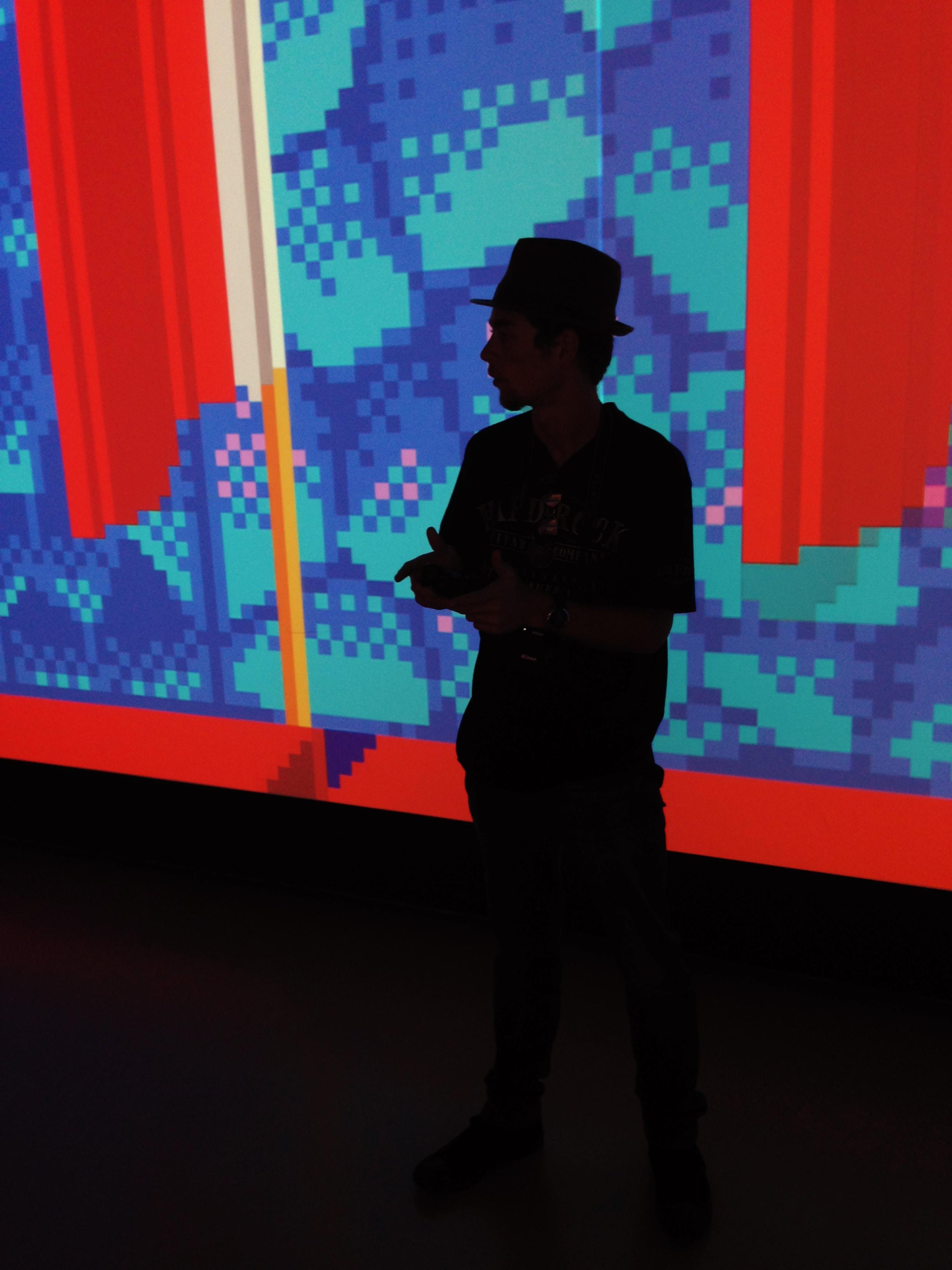 silhouette of man near multicolored wall