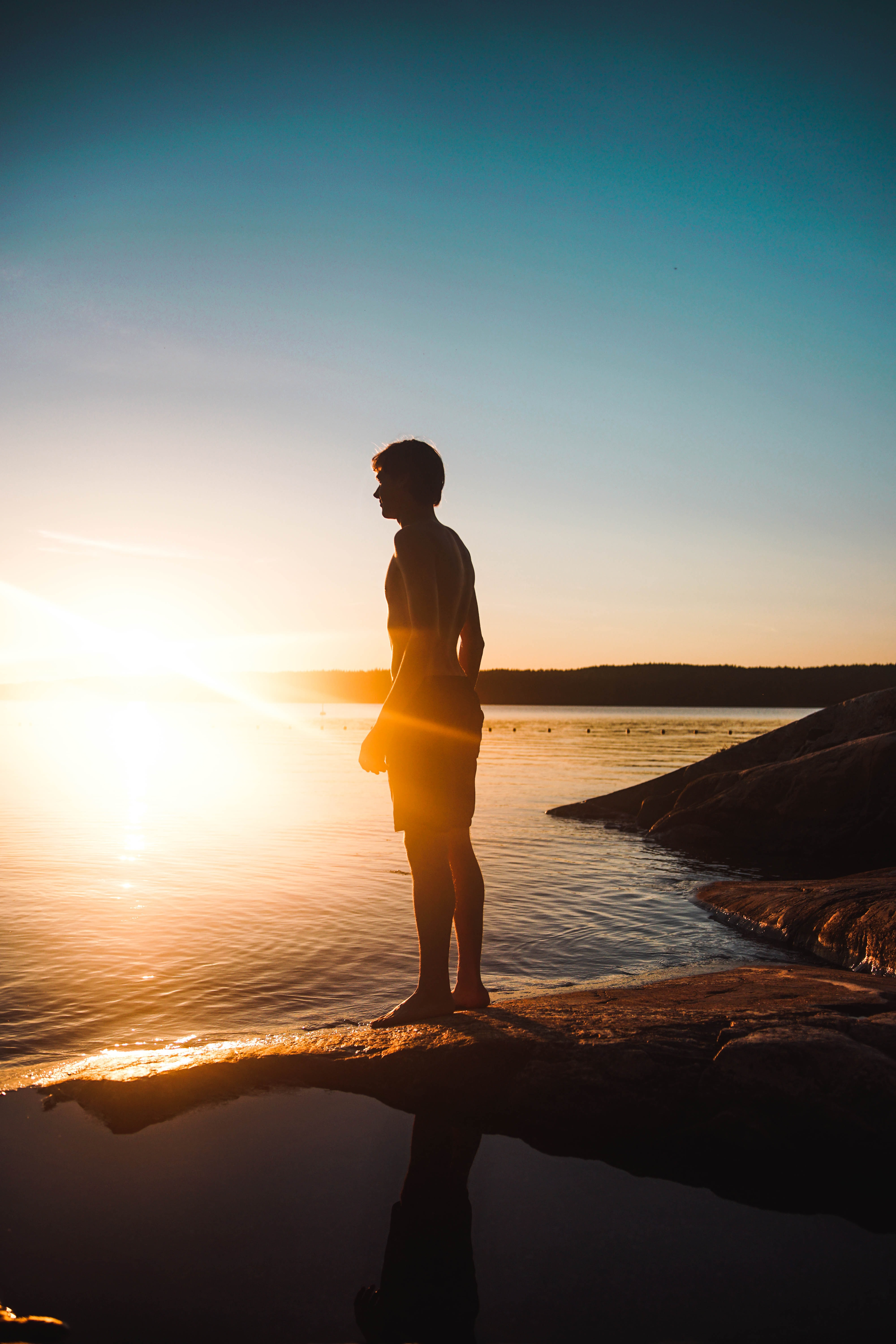 man standing on rock besides body of water during sunset
