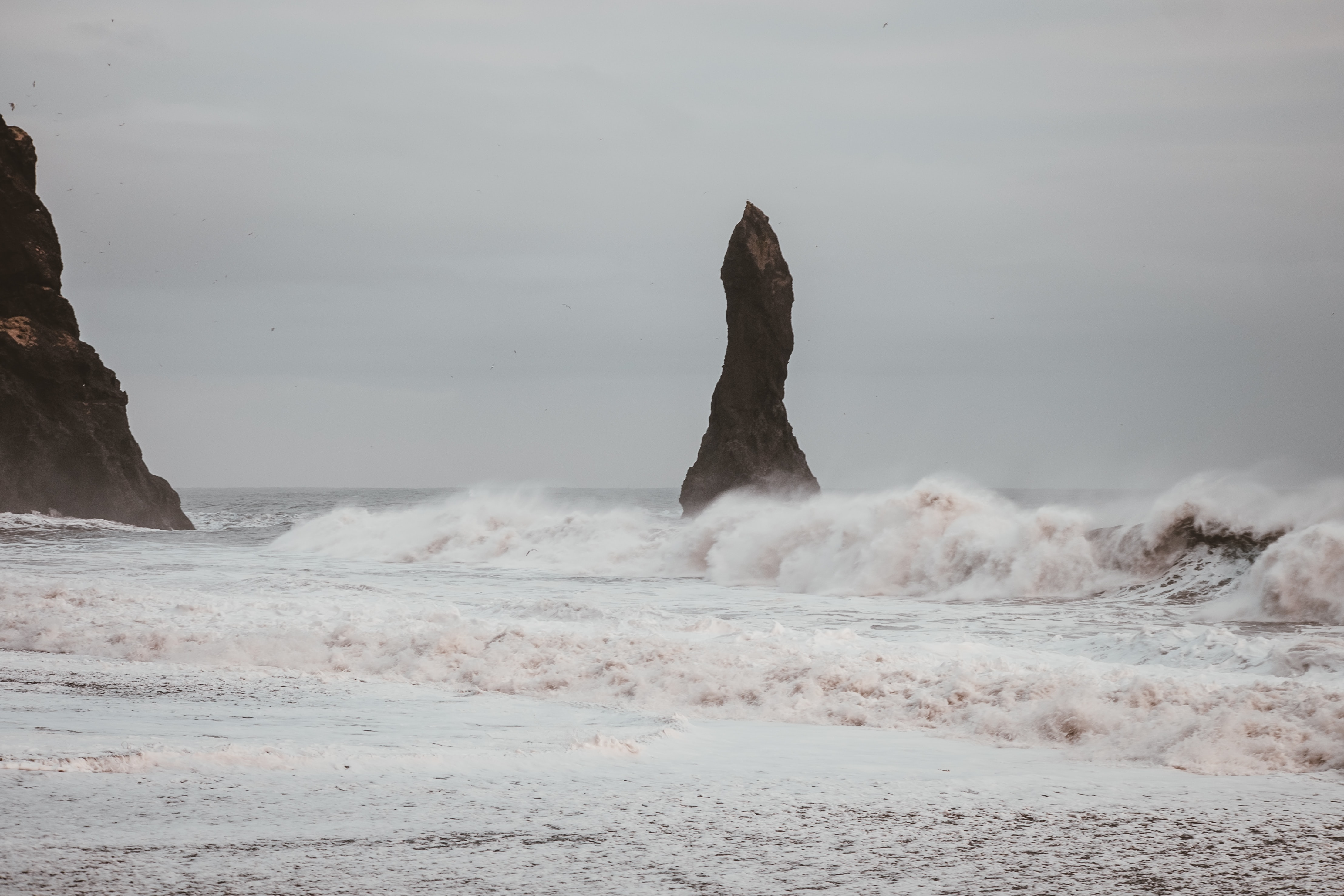 ocean waves move near rock formation under cloudy sky