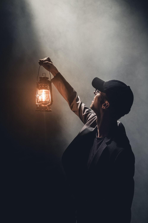man holding lighted gas lantern