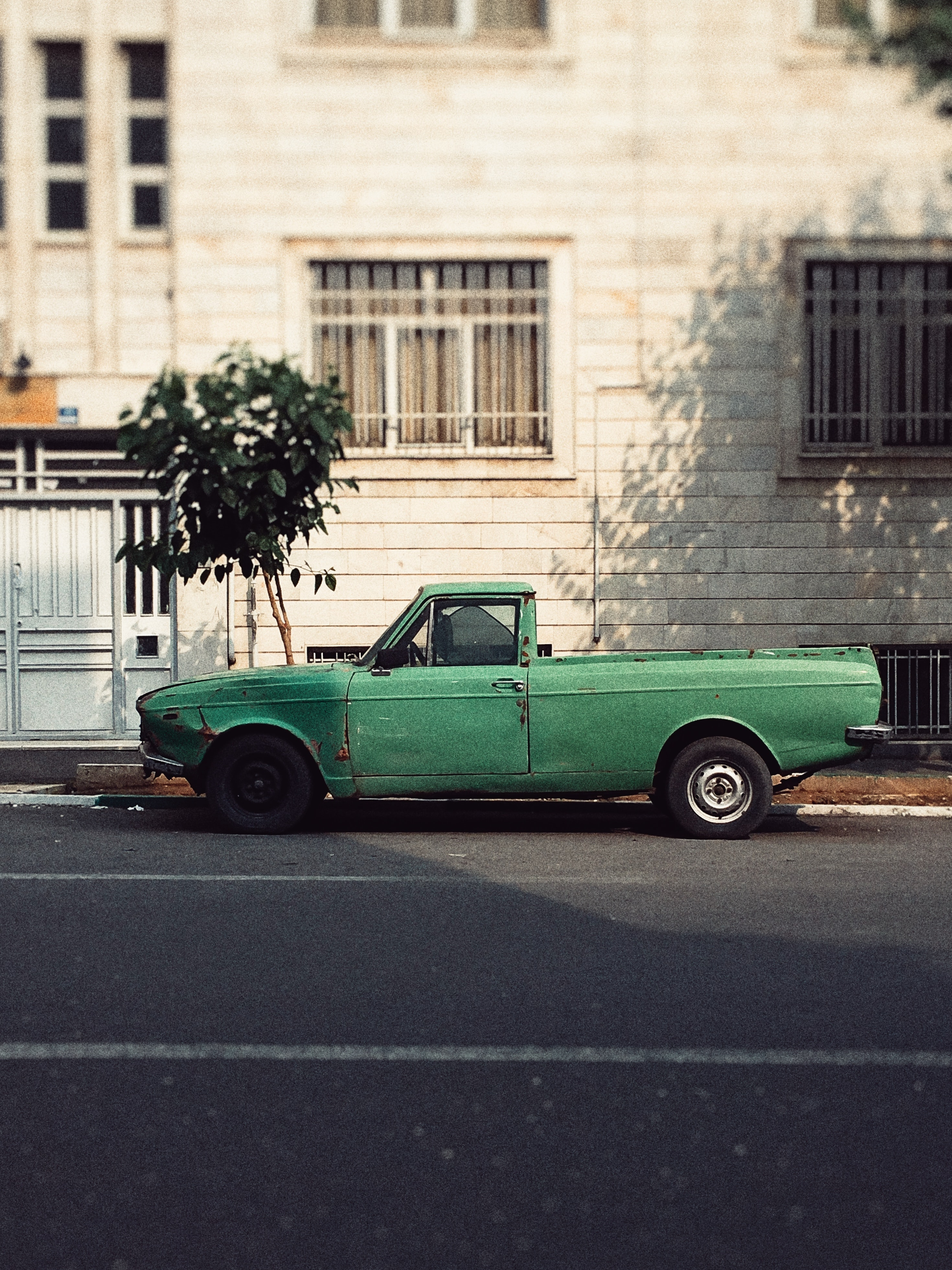 green single cab pickup truck parked beside building