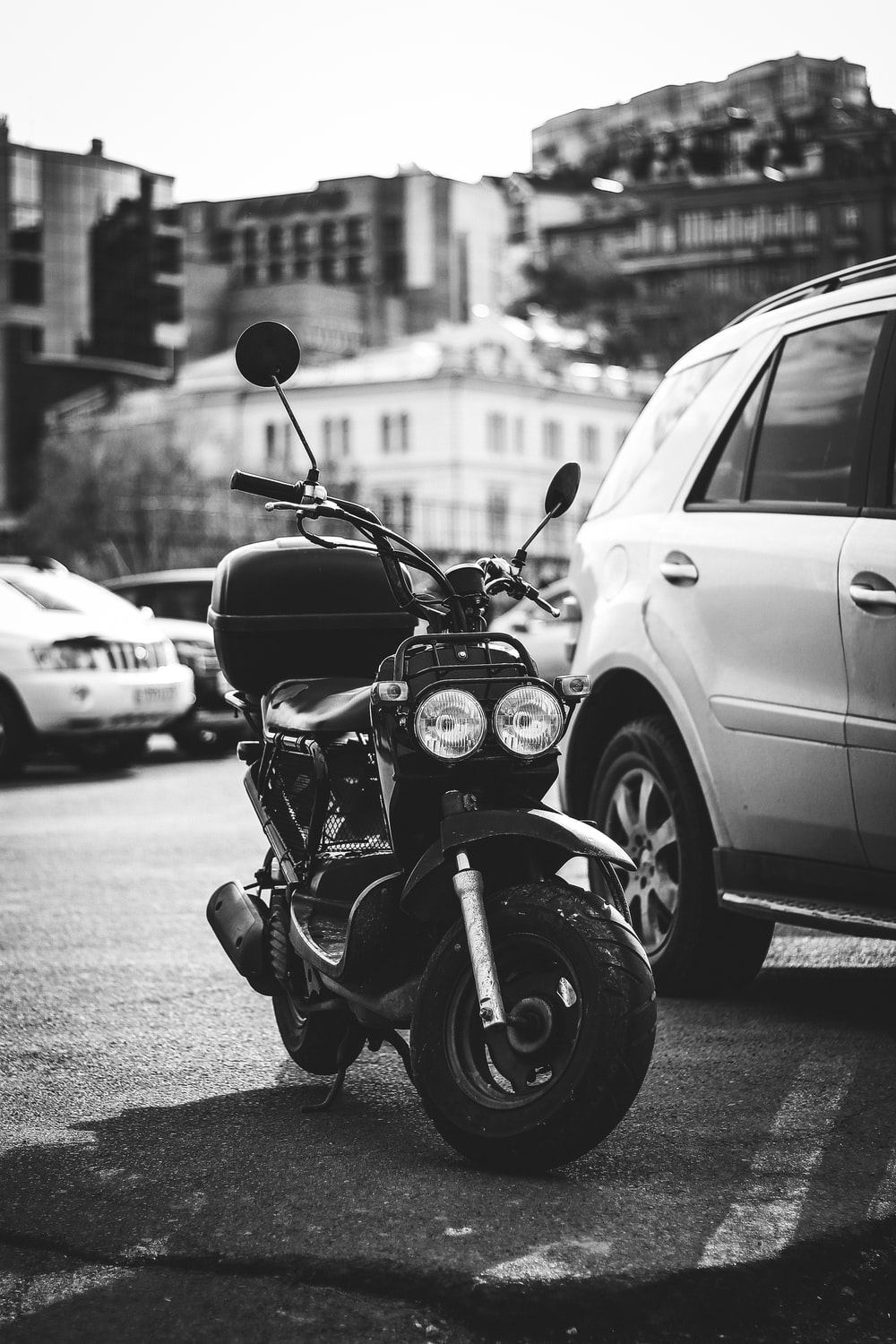 grayscale photography of scooter beside car