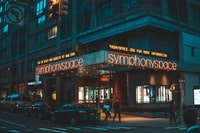 people walking beside Symphony Space store during night time