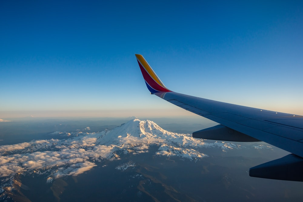 commercial airplane wing view fly over alpine mountain