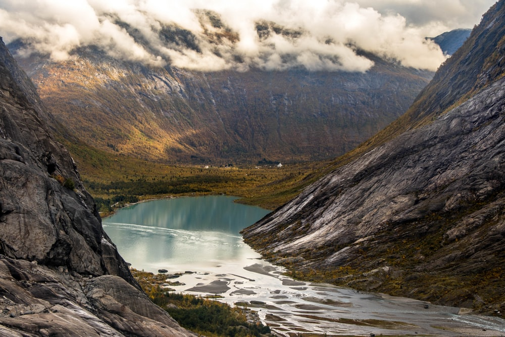 landscape photography of body of water between mountain