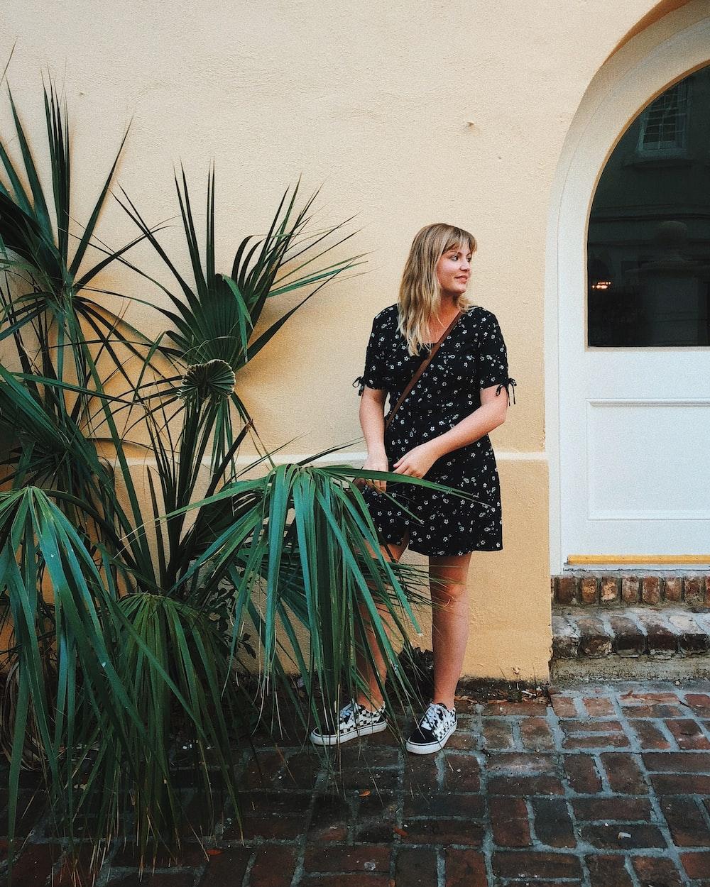 woman wearing mini dress beside beige wall