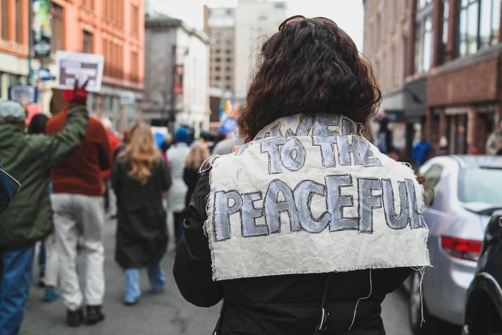 woman with to the peace signage at her back facing people