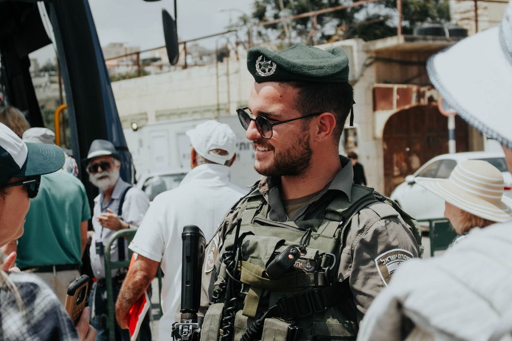 smiling man wearing soldier uniform standing near crowd during daytime