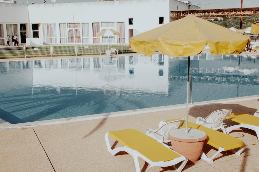 lounger and patio umbrella near pool