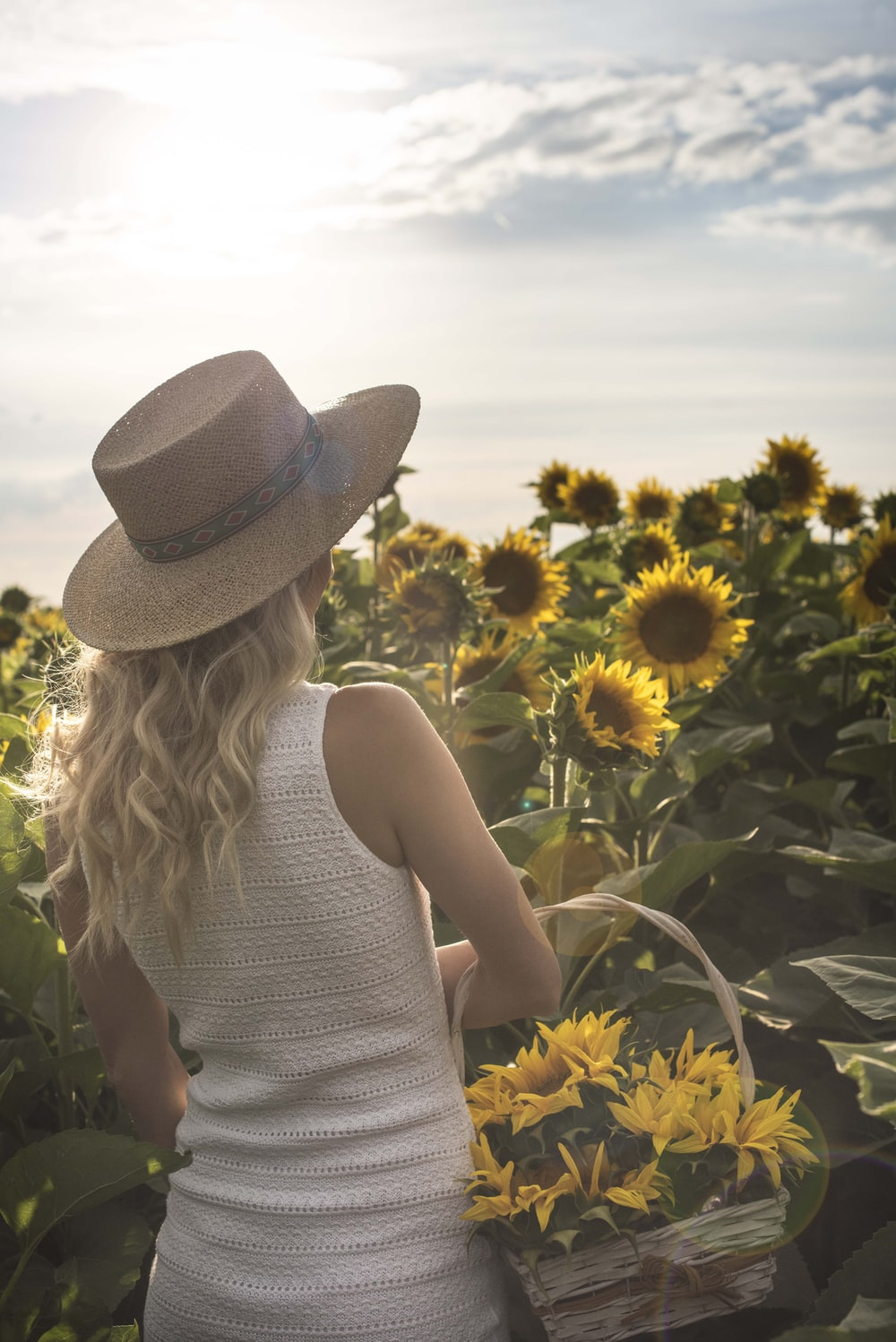 woman standing holding basket front of sunflower