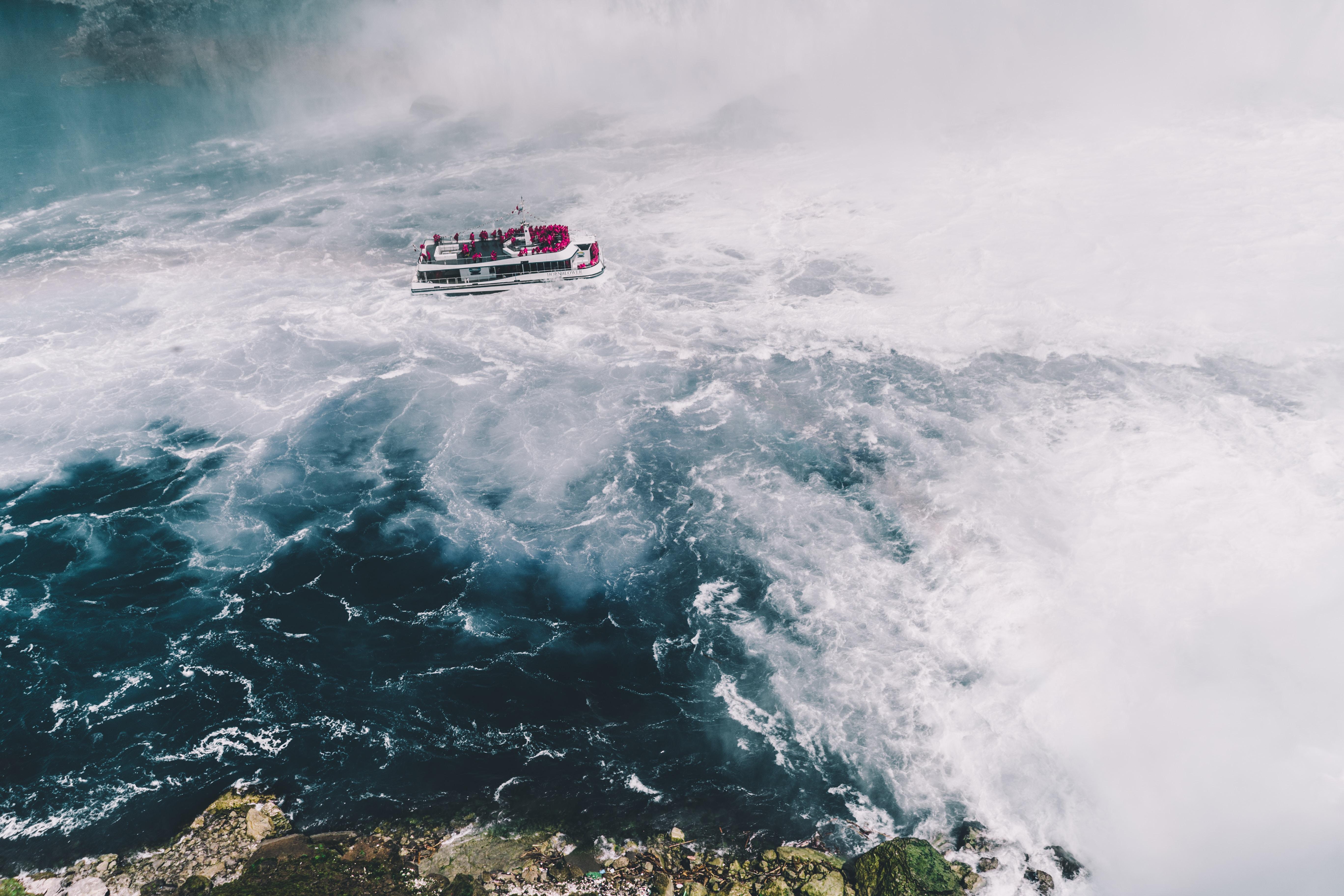 ship on body of water near waterfalls