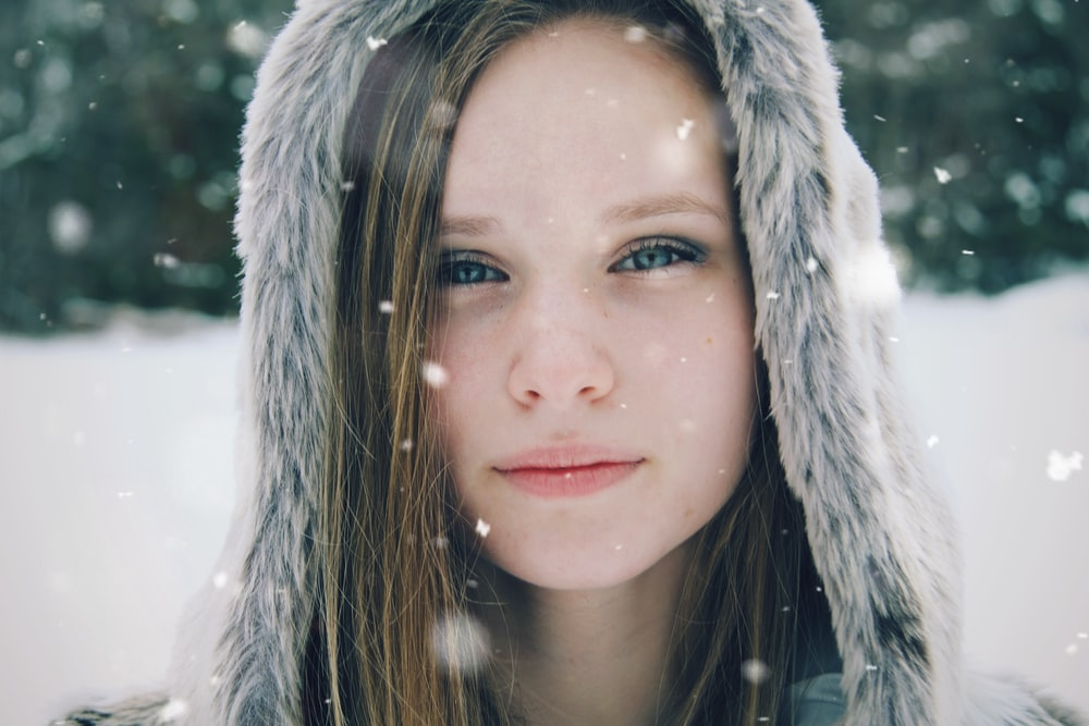 focus photo of a woman's face wearing parka hoodie