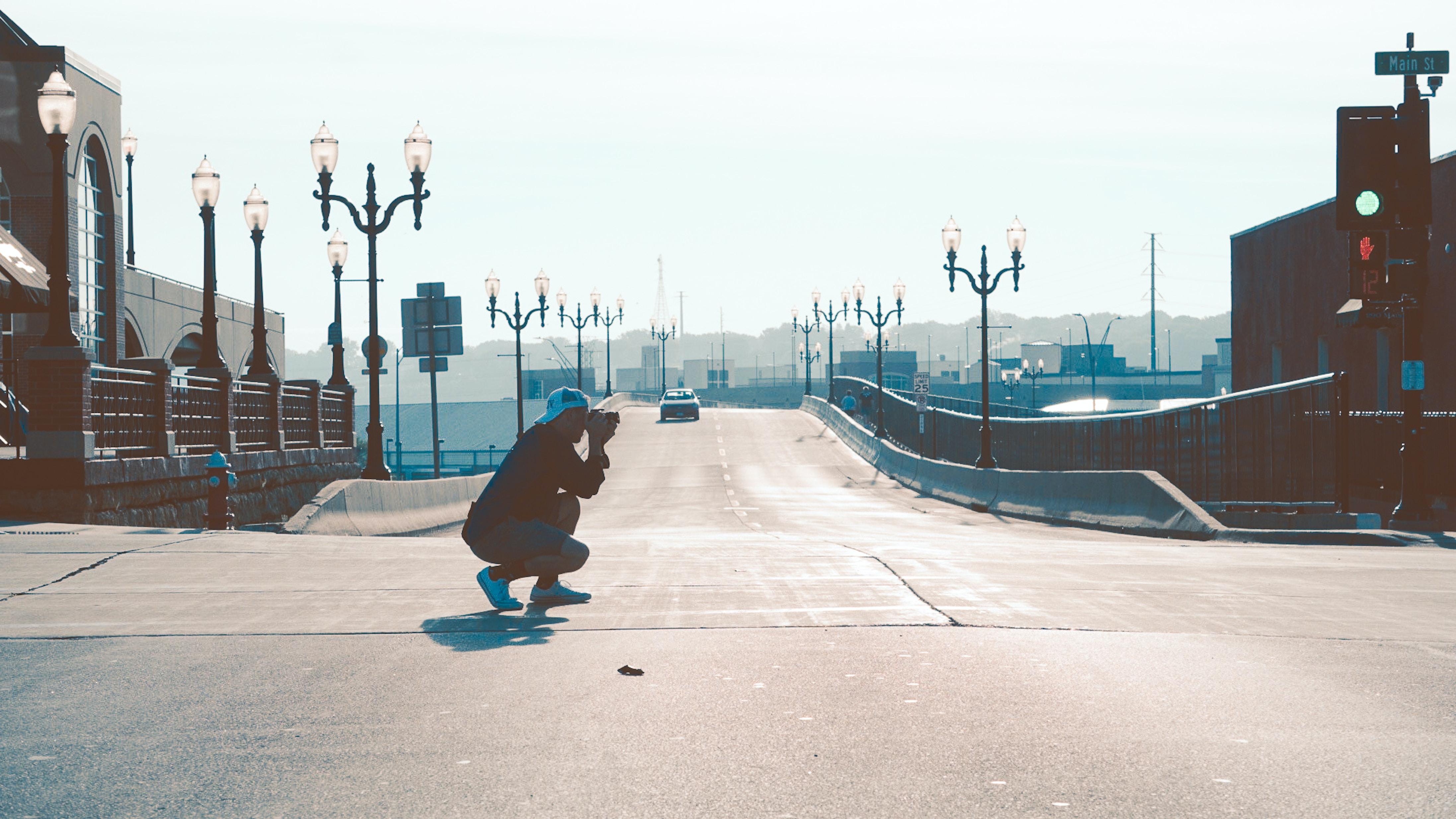 man squatting on road while taking photo
