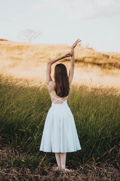 woman wearing white sleeveless dress standing near grass at daytime