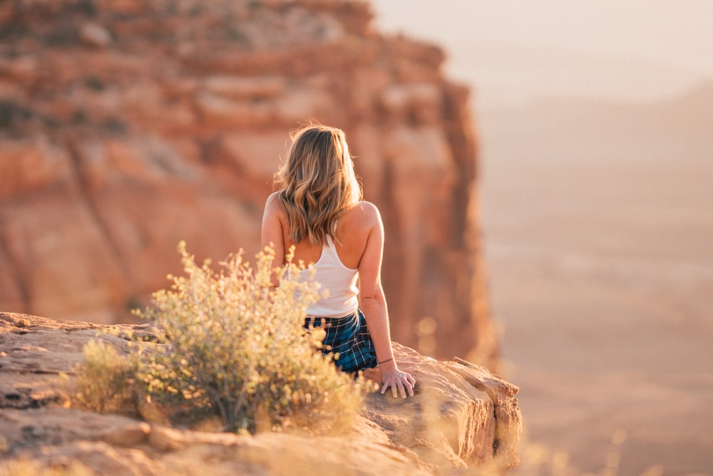 woman sitting on cliff during daytime
